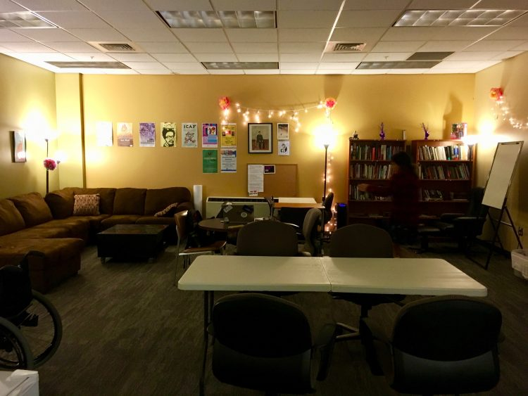 A wide view of the D Center in MGH 024, warmly lit with posters and fairy lights strung on the wall. To left is a brown sectional couch, in the center are meeting tables with chairs, and to the right are two bookcases filled with books and games.