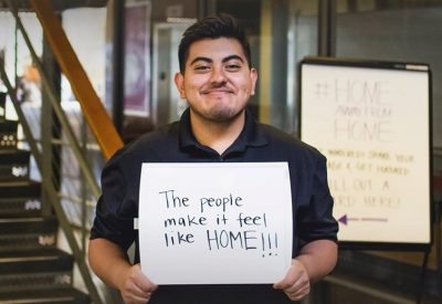 "A student holding a sign that says ""The people make it feel like home!"" for our Home Away From Home Campaign that asks why students love the Kelly ECC"