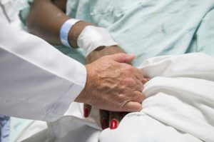 A doctor holds the hands of a burn patient with a bandaged wrist at Harborview Medical Center.