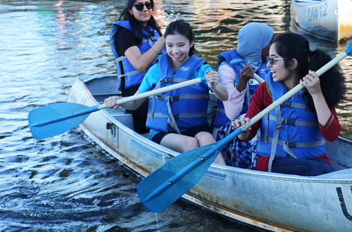 INSIGHT interns paddle a canoe at the HIPRC Summer Picnic.