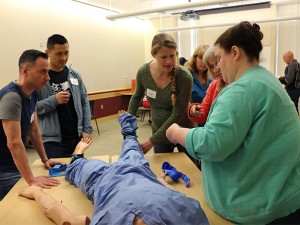 Participants observe a instructor demonstrating proper use of a tourniquet on a medical simulation mannequin.