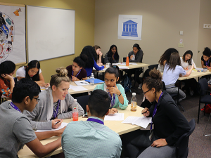 INSIGHT interns work in groups at tables, discussing an epidemiology exercise.
