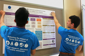 Two students in blue HIPRC T-shirts hang a research poster on a display board.