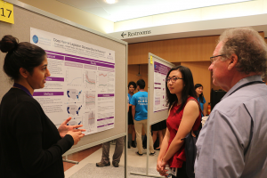 An HIPRC INSIGHT students presents a research poster to two symposium attendees in 2017.