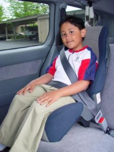 A child in a high-back booster seat, with the seat positioning the seat belt correctly over the lower hips and the center shoulder.
