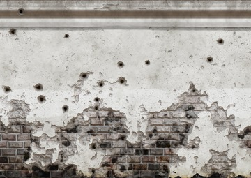 Crumbling pale brick and plaster wall with bullet holes scattered throughout.