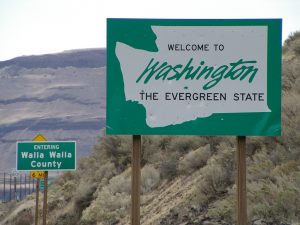 Highway signs along road through the hills: Welcome to Washington, The Evergreen State. Entering Walla Walla County.