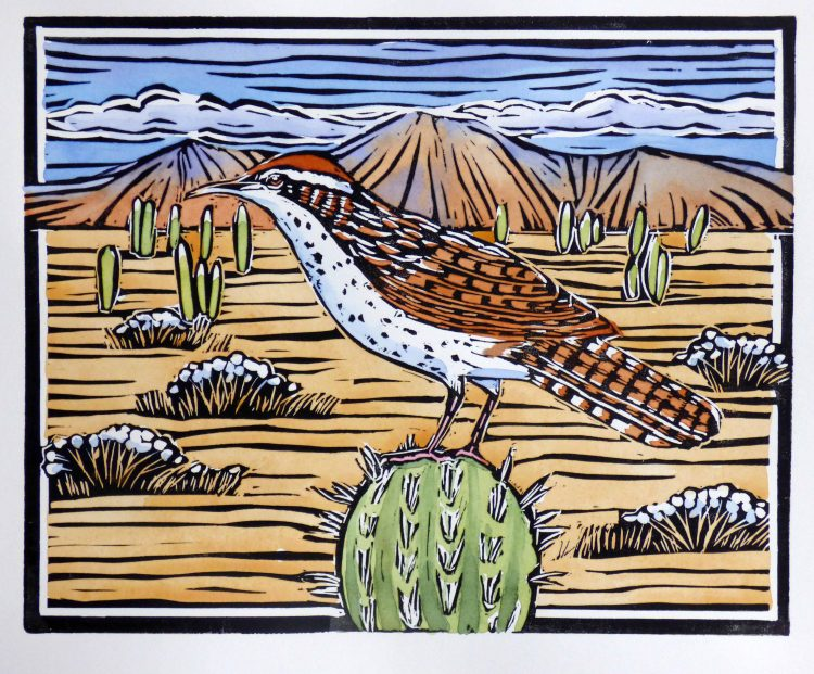 wren perched on a cactus with mountains in the background