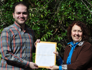 Student and staff member holding the last paper thesis ever submitted.