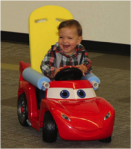 Child laughing and driving adapted toy car by pressing both hands on central red button