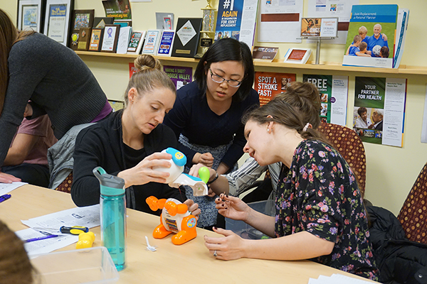 Three individuals sit at a table. They are all huddled around a children's toy which is opened up.