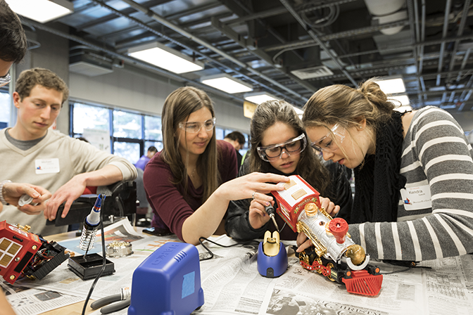Four individuals working at a table. They are huddled around a toy train that has been opened up to reveal the electronics inside. One individual holds a soldering iron and is getting ready to solder inside the toy