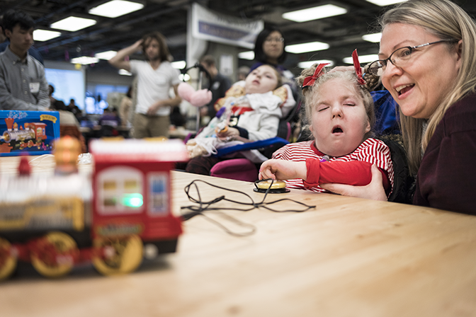 A young girl and her mother sitting at a table. The young girl is ipressing a button. Both are looking at a toy train in the foreground which is activating as the button is pressed.