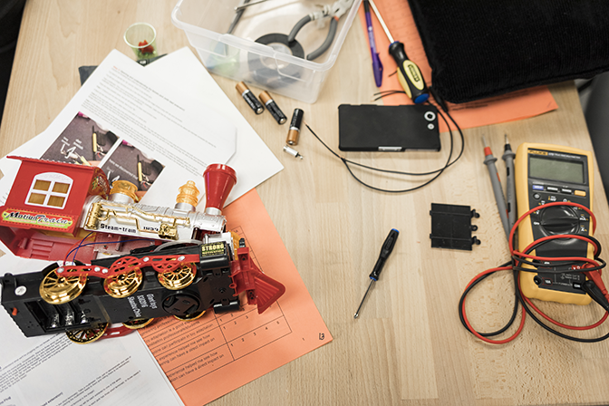 A top down view of a toy train sitting on a table next to a digital multimeter. The train is open and in the process of being adapted