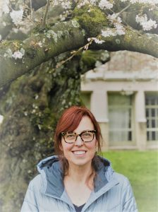 A woman with red hair and glasses wearing a gray jacket and standing outside in front of a cherry blossom tree