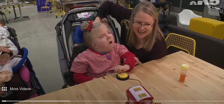 A young girl in a wheel chair sits with her mom at a table. The girl has a yellow button in front of her that she is pressing. A toy train sits on the table, connected to the button.