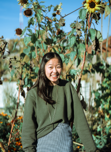 Alicia in a green sweater smiling in a field of tall sunflowers.