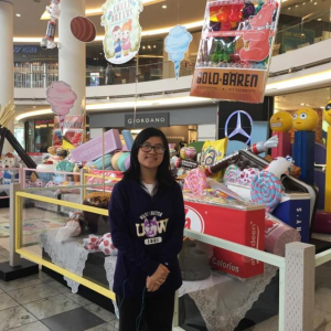 Sam in a black sweatshirt smiling in front of a candy display