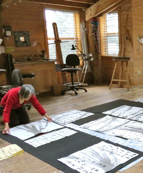individual in an art studio space kneels on the floor, laying out a series of paintings on paper