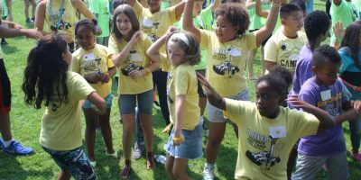 a group of many active youths in a field dancing and jumping around together, all wearing yellow, purple, blue, or green tshirts that read: Miller Summer Day Camp
