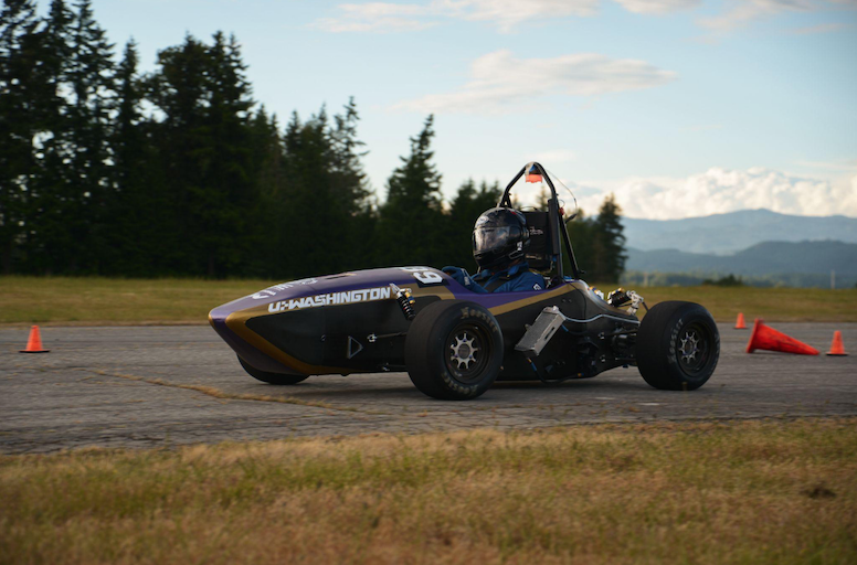A small race car idles on pavement, set against a forested landscape, blurred mountains and clouds visible in the background.