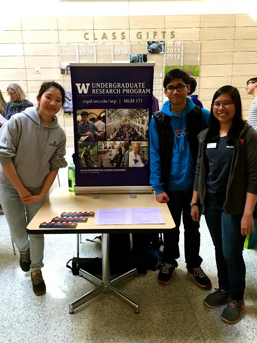 A group of three students stand in front of a tabling set up, which features flyers and a stand up poster advertising the Undergraduate Research Program.