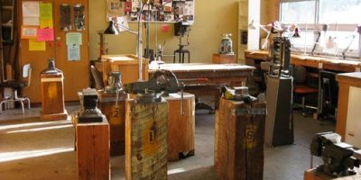 Sun shines through a large window of a small jewelry working studio. Several small anvils sit in the center of the studio space, with a table and cabinets in the back.