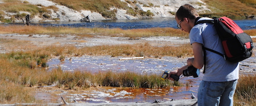 UW AB student Michael Diamond checks the water's temperature in Yellowstone