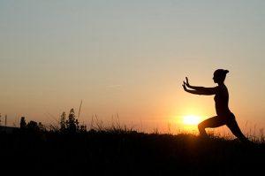 Woman doing taichi at sunrise