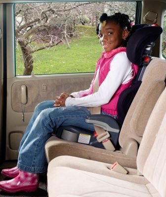 A girl seated in a booster seat with seat belt fastened.