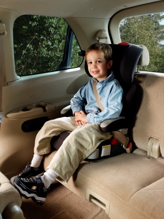 A child seated in a high-back booster seat with seat belt fastened.