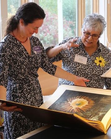 Tracy Mehlin discusses a rare book with local artist Sylvia Portillo