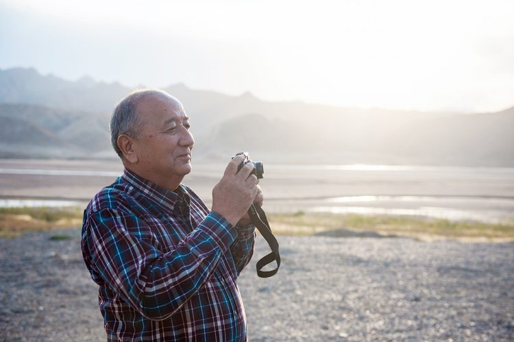 Older Chinese man holding a camera on the beach