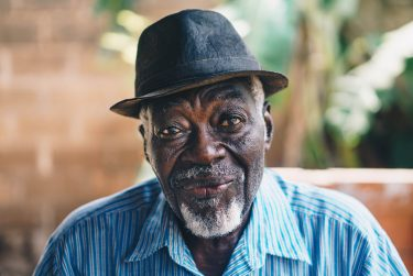 Older black man wearing a hat and blue shirt