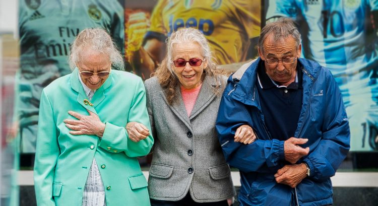 three white, older adults cross the street together; two are woman and one is a man.