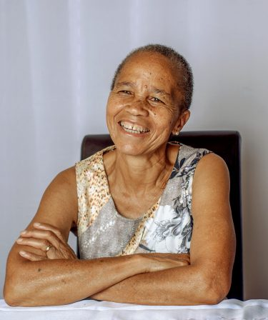 older black woman with short hair and a tank top sitting at a table smiling