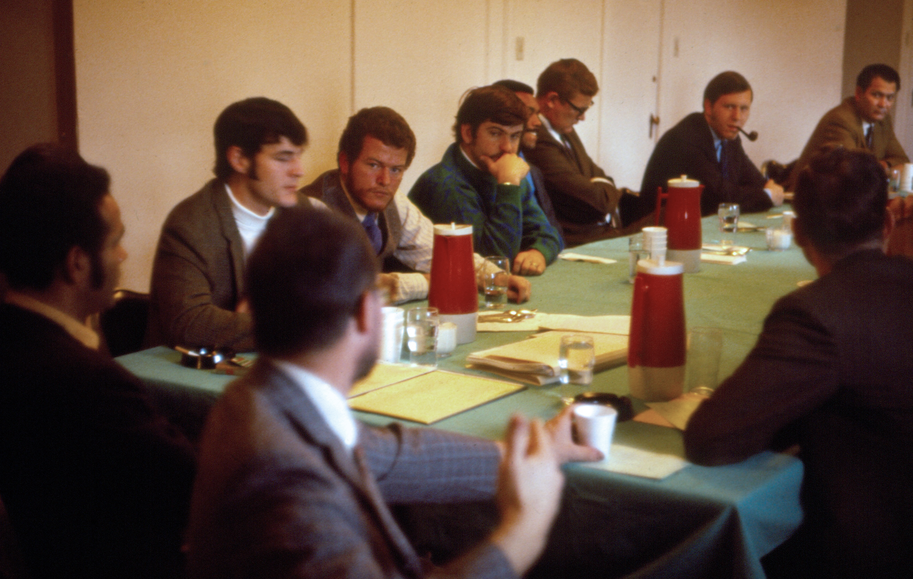 A meeting of the students and faculty of MEDEX in 1969. Dr. Richard Smith is to the far left. John Betz is at the right with a pipe.