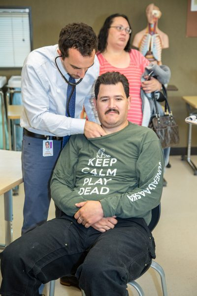 MEDEX PA student Chris Pitre of Seattle Class 50 listens to a patient's heart during a preliminary health screening.