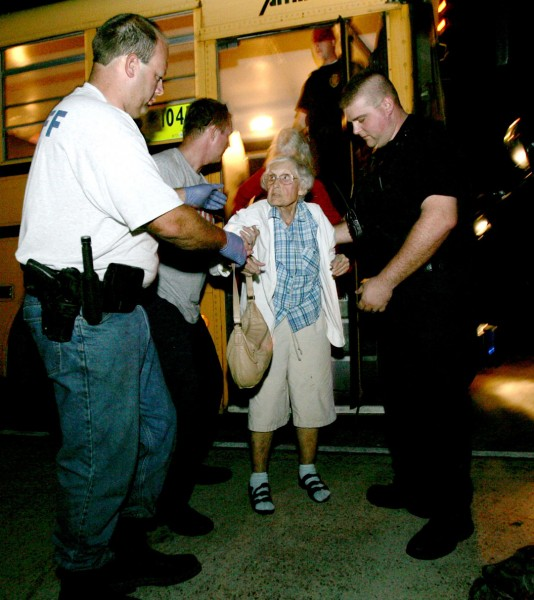 Photo of a sheriff's officer from helps a woman exit a bus at a shelter after Hurricane Gustav.