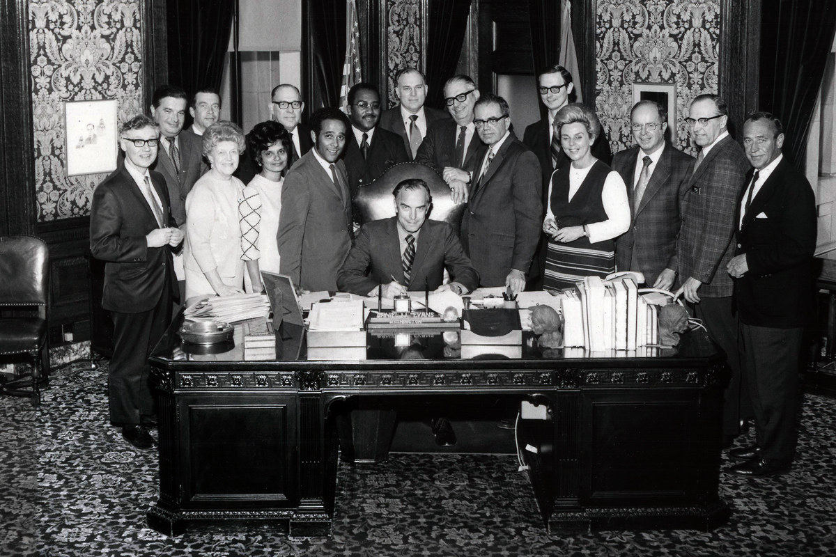 Washington State Governor Dan Evans signed into law the MEDEX enabling legislation on April 14, 1971. Smith is pictured to the left of the seated Governor.