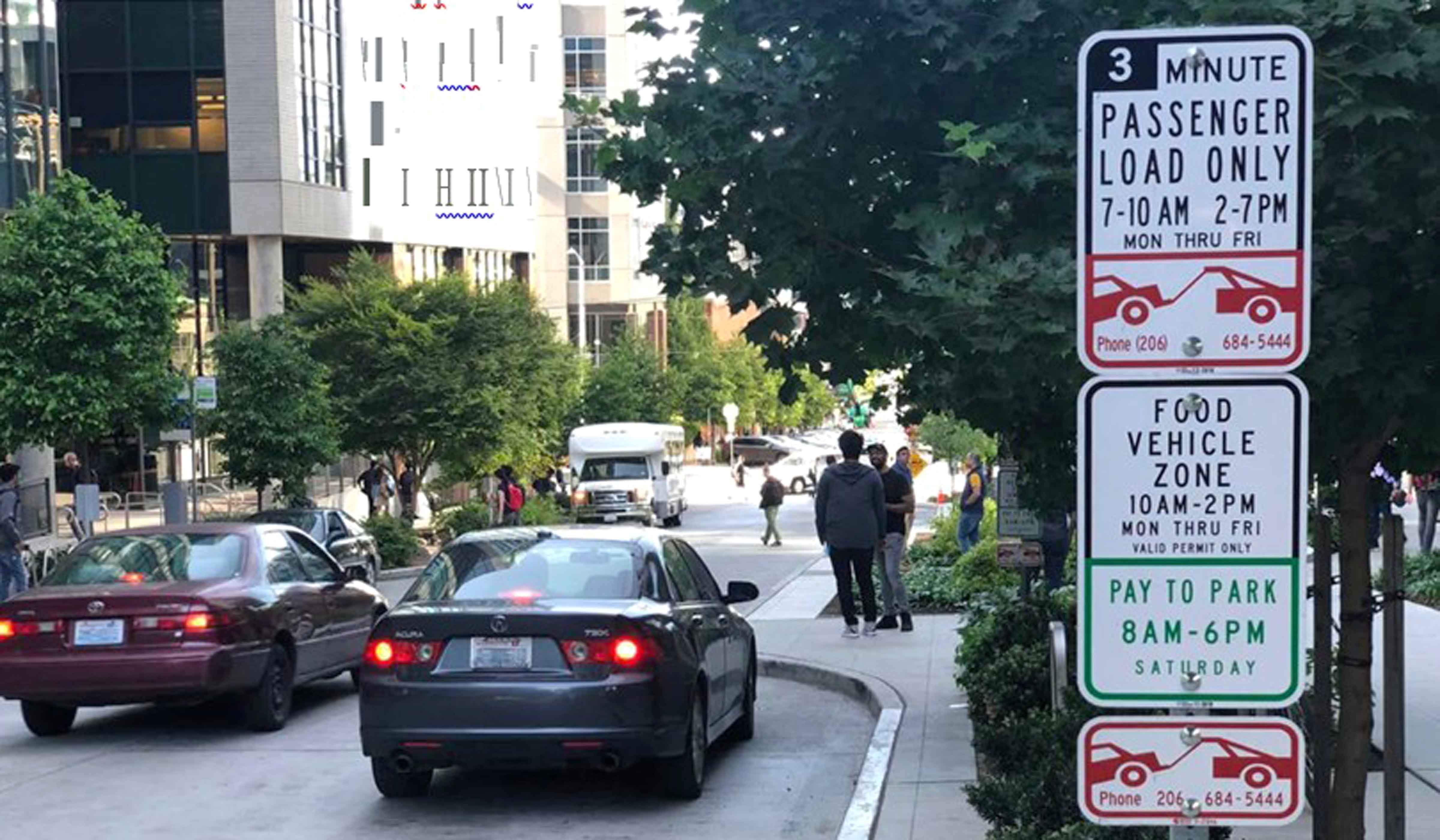 """This photograph shows a loading zone in Seattle with a sign reading, """"3-minute passenger load only 7 to 10 am and 2 to 7 pm Monday through Friday"""" and """"Food vehicle zone 10 am to 2 pm Monday through Friday, valid permit only"""""""